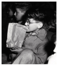 Boy eating popcorn in a cinema.